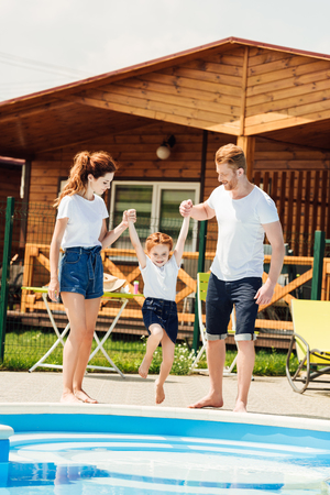 beautiful young family playing at poolside of cozy wooden cottage 版權商用圖片