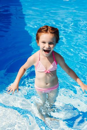 laughing little child in bikini in swimming pool Stock Photo