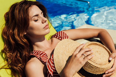 close-up portrait of attractive young woman relaxing on sun lounger at poolside