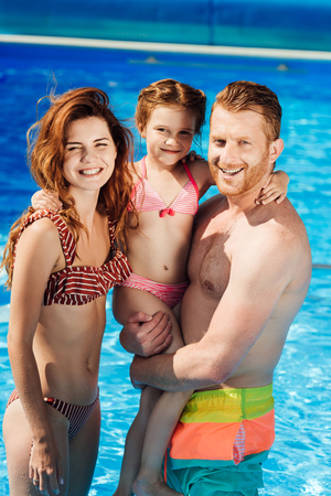 beautiful young family embracing in swimming pool and looking at camera