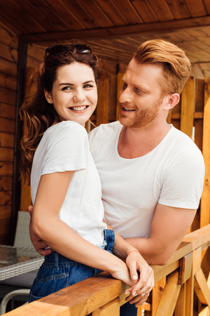 happy young cuddling couple in white t-shirts on terrace of wooden cottage Stock fotó