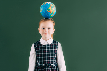 adorable little schoolgirl with globe on head standing near blackboard and smiling at camera 免版税图像