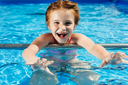 close-up portrait of adorable little child in bikini in swimming pool looking at camera