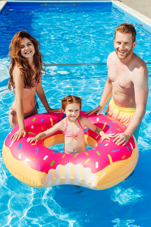 smiling young parents with daughter floating in rubber ring looking at camera at swimming pool