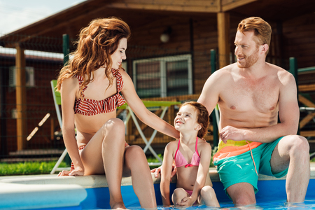 beautiful young family sitting at poolside together