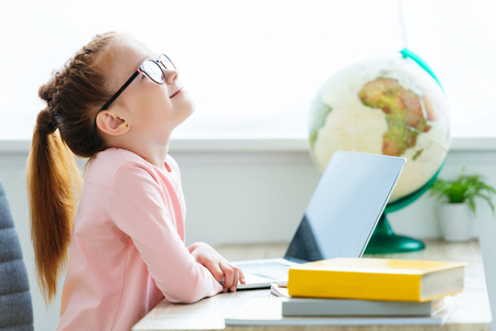 side view of smiling red haired schoolgirl in eyeglasses using laptop at desk