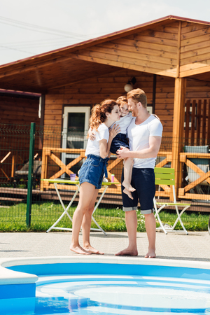 beautiful young family embracing at poolside of cozy wooden cottage