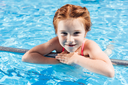 close-up portrait of happy little child in bikini in swimming pool looking at camera