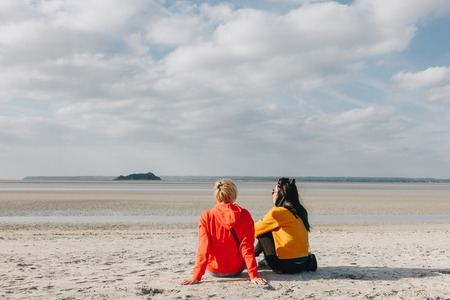 back view of girls sitting on sandy beach, Saint michaels mount, Normandy, France Stockfoto