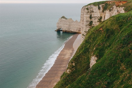 aerial view of scenic rocky cliff with green grass on foreground at Etretat, France