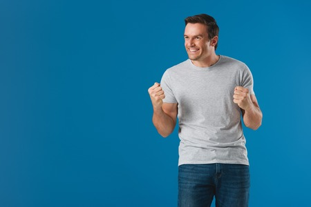 happy man shaking fists and looking away isolated on blue