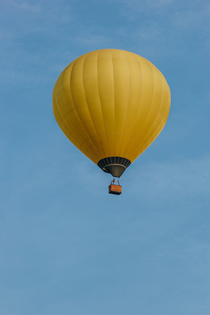 bottom view of yellow hot air balloon flying in blue sky
