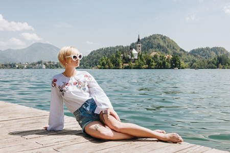 beautiful young woman in sunglasses resting on wooden pier at scenic mountain lake, bled, slovenia
