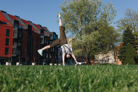athletic stylish young woman doing side somersault on grass in park