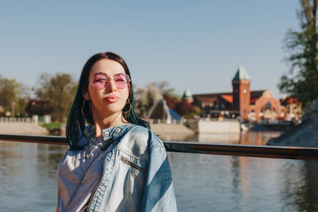 close-up portrait of young woman in stylish clothes on sunset in wroclaw, poland