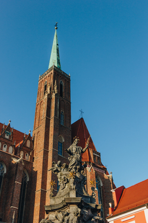 bottom view of Church of Holy Cross tower with St Bartholomew statue, Wroclaw, Poland