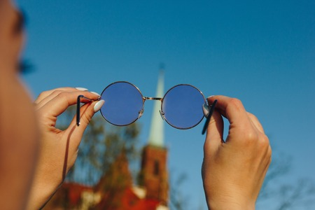 cropped shot of woman holding stylish sunglasses and looking through Zdjęcie Seryjne