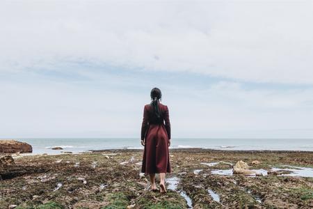 back view of elegant barefoot girl on rocky shore near the sea, Etretat, Normandy, France