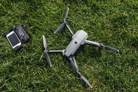 top view of drone and controller with smartphone on green grass Stockfoto