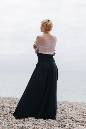 back view of stylish girl posing on shore near sea, Etretat, Normandy, France