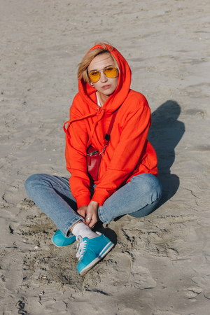 stylish girl in red hoodie sitting on sandy beach, Saint michaels mount, Normandy, France Stock Photo