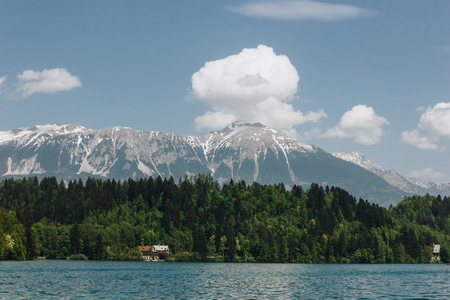 majestic landscape with snow-covered mountain peaks, green trees and tranquil mountain lake, bled, slovenia