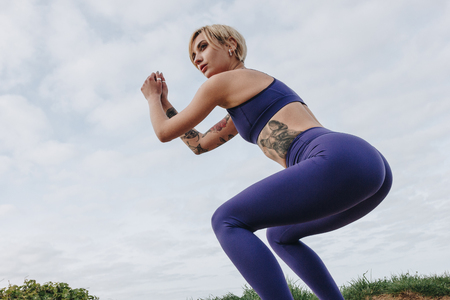 attractive sportswoman squatting in stylish sportswear, Etretat, France