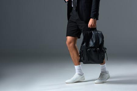 cropped image of stylish man in shorts holding backpack on grey background Stock Photo