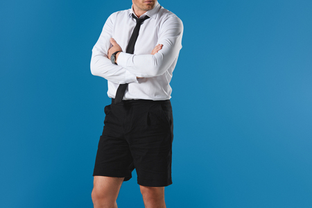 cropped image of stylish man in shorts with crossed hands isolated on blue background Stock Photo