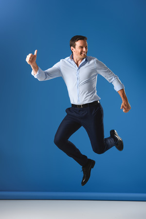 cheerful handsome man showing thumbs up and jumping on blue Stock Photo