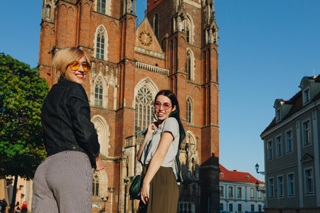 two attractive smiling women standing in front of wroclaw cathedral and looking at camera Zdjęcie Seryjne