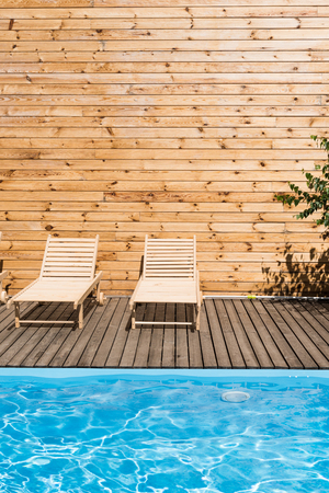 empty cozy chaise lounges near swimming pool with transparent water Stock Photo