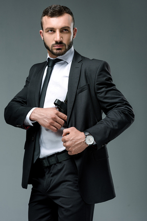 handsome security guard taking gun isolated on grey