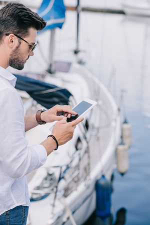 cropped shot of young man in sunglasses using digital tablet at yacht