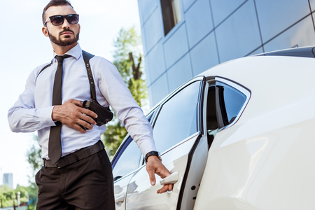 handsome bodyguard touching gun and opening car door