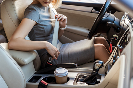 cropped image of businesswoman fastening safety belt in car Imagens