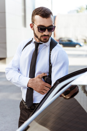 handsome security guard touching gun and opening car door