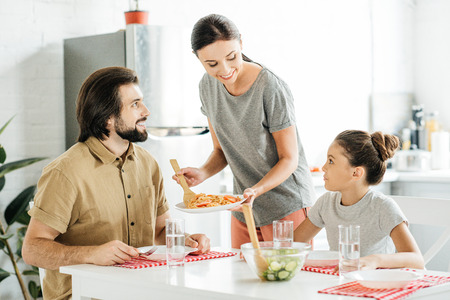 attractive young mother with tasty breakfast for daughter and husband at kitchen