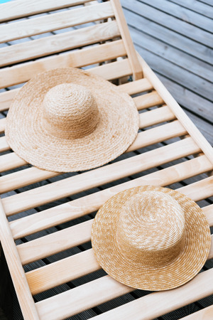 two stylish wicker hats on chaise lounge at poolside