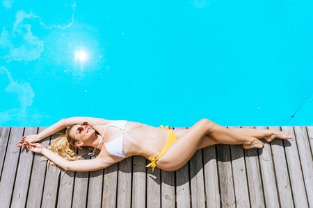 high angle view of beautiful blonde woman in bikini and sunglasses resting near pool