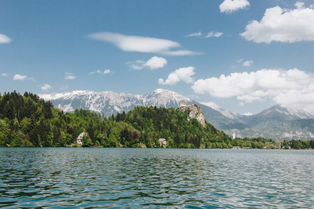 beautiful landscape with snow-covered mountain peaks, green vegetation and calm lake, bled, slovenia 免版税图像