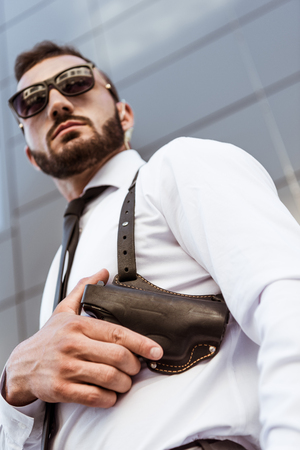 low angle view of handsome bodyguard in sunglasses touching gun and looking away Stock Photo