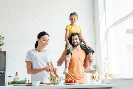 smiling young woman preparing salad while her daughter riding on shoulders of husband at kitchen