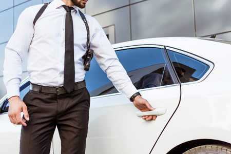 cropped image of security guard with gun opening car door