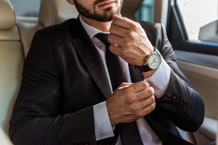 cropped image of businessman buttoning cuff in car