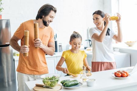 Hermosa joven familia tocando música con utensilios de cocina y divirtiéndose en la cocina