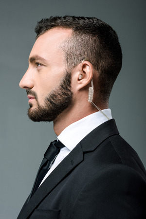 profile of handsome security guard with security earpiece isolated on grey