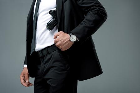 beschnittenes Bild des Wachmanns, der mit der Waffe steht, die auf grau lokalisiert wird Standard-Bild