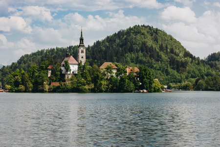 majestic view of mountains covered with green trees, calm lake and old buildings, bled, slovenia