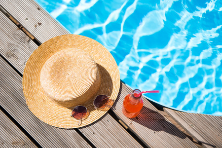 top view of wicker hat, sunglasses and bottle with summer drink near swimming pool 스톡 콘텐츠